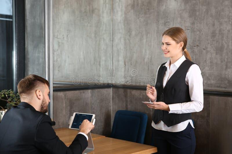 Młoda kelnerka bierze rozkaz od mężczyzny w restauracji obraz royalty free