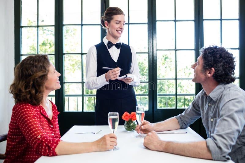 Młoda kelnerka bierze rozkaz od pary zdjęcia stock