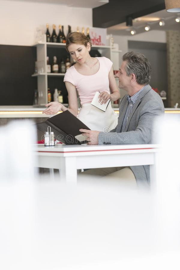 Młoda kelnerka pomaga dojrzałego klienta z menu przy restauracją zdjęcie stock