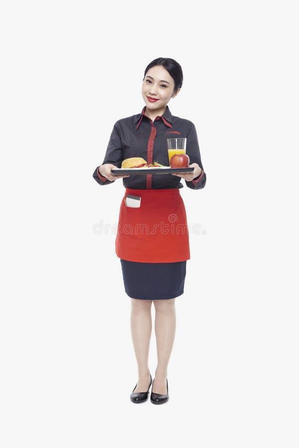 Młoda kelnerki przewożenia taca z jedzeniem, studio strzał zdjęcie royalty free