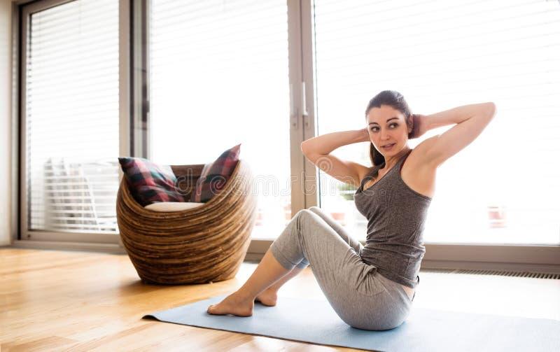 Młoda kobieta ćwiczy w domu, robić chrupnięciu zdjęcie royalty free