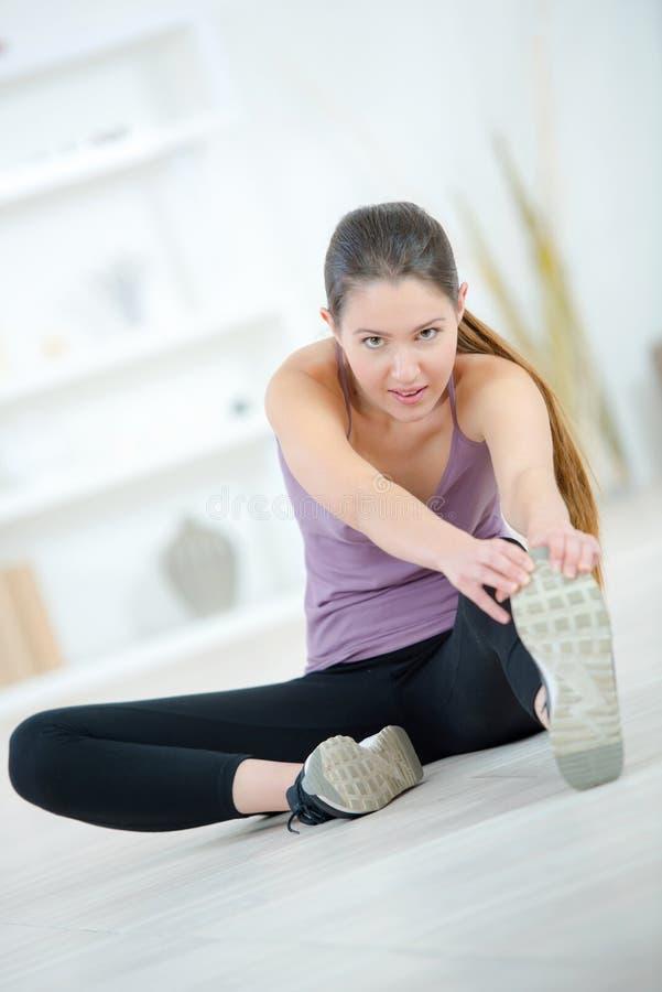 Młoda kobieta ćwiczy w domu rozciągać nogi zdjęcie royalty free