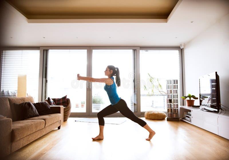 Młoda kobieta ćwiczy w domu, rozciągający iść na piechotę i ręki zdjęcie stock