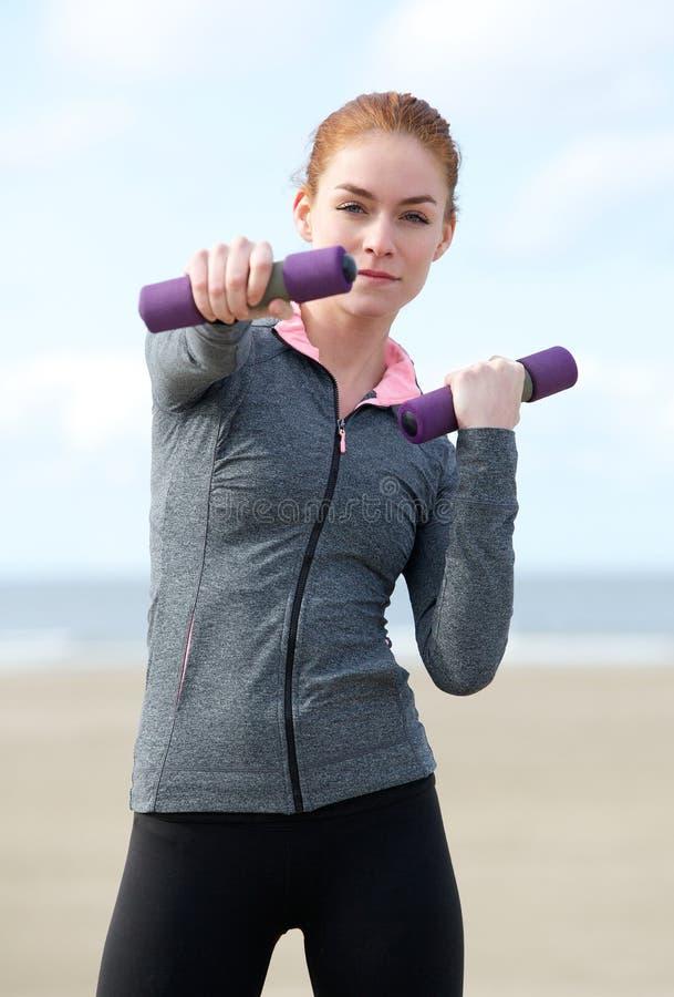 Młoda kobieta ćwiczy z ciężarami outdoors obrazy stock