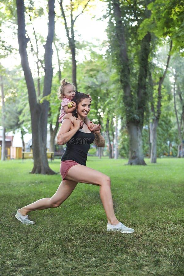 Młoda kobieta ćwiczy z jej dziewczynką w parku zdjęcia royalty free