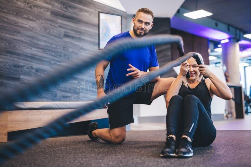 Młoda kobieta ćwiczy z osobistym trenerem przy gym obrazy stock