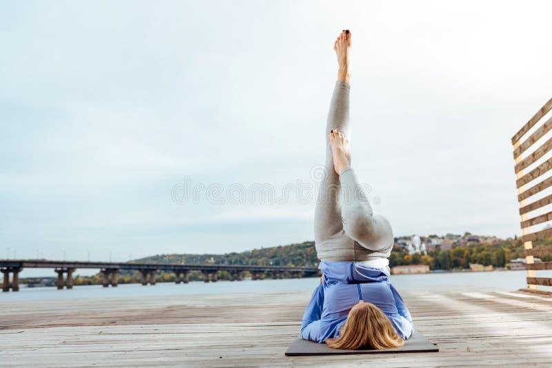 Młoda kobieta łatwo wykonuje Podtrzymanego Shoulderstand plenerowego zdjęcia royalty free