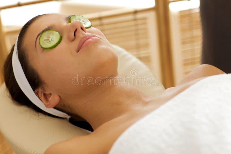 Młoda kobieta łgarski puszek w masażu stole z ogórkami na oczach fotografia stock