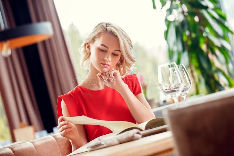 Młoda kobieta łomota w restauracyjnym siedzącym patrzeje menu rozważnym zdjęcie stock