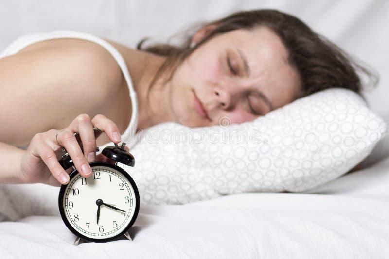 Młoda kobieta śpi w łóżku i obraca daleko alarm Sen po budzika dzwonił dziewczyna budzi się up na budziku w wczesnym poranku obraz royalty free