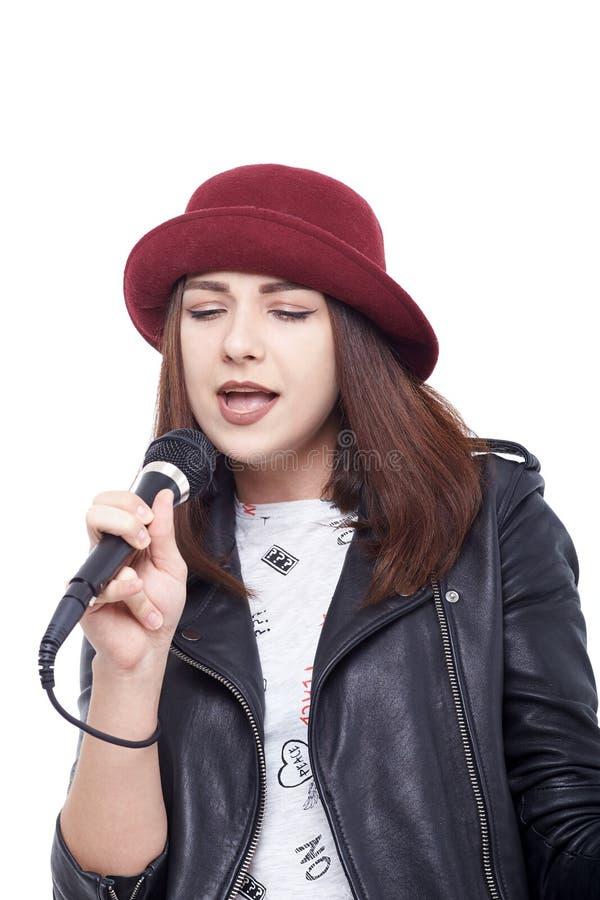 Młoda kobieta śpiew z mikrofonem jest ubranym białą koszulkę obraz stock