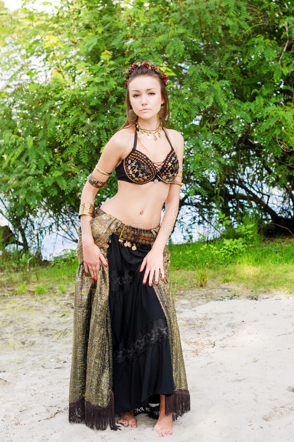 Młoda kobieta amerykanina stylu plemienny tancerz Dziewczyna taniec i pozować na plażowym piasku jest ubranym brzucha tana kostiu obraz stock