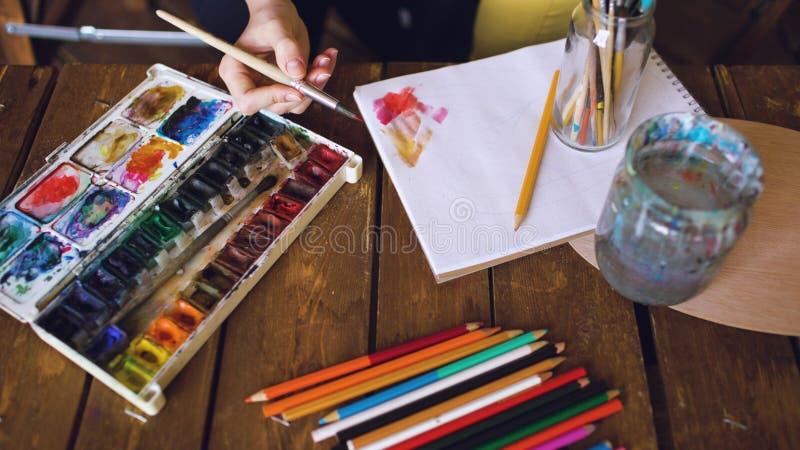 Młoda kobieta artysty remisu pictrure z akwareli farbami miesza koloru zbliżenie muśnięciem i fotografia royalty free