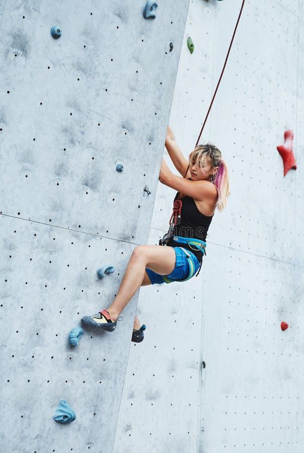 Młoda kobieta arywista wspina się na otwartym wspinaczkowym gym zdjęcia stock