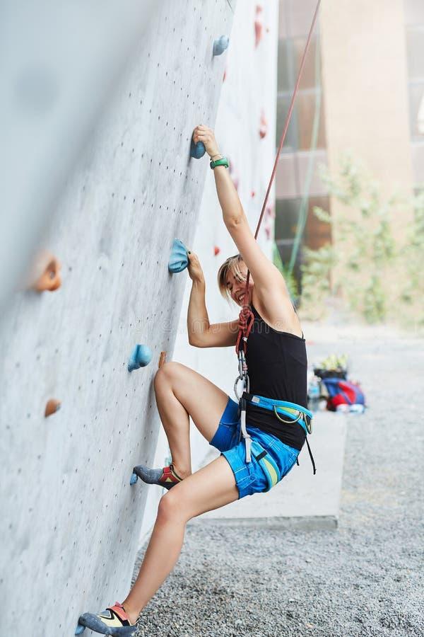 Młoda kobieta arywista wspina się na otwartym wspinaczkowym gym fotografia stock