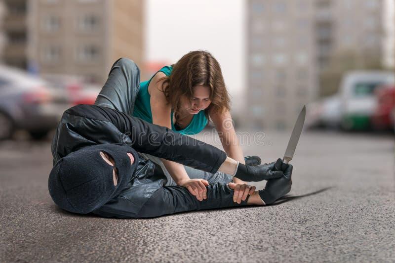 Młoda kobieta atakował orężnym złodziejem i jest walcząca i broniąca zdjęcia stock