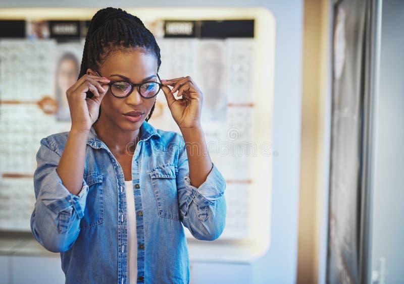 Młoda kobieta bada napad dla eyeglasses zdjęcie royalty free