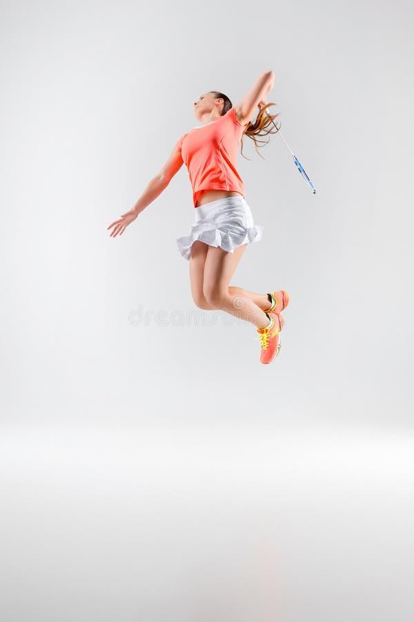 Młoda kobieta bawić się badminton nad białym tłem obraz royalty free