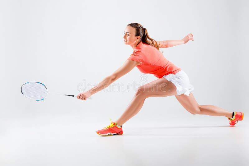 Młoda kobieta bawić się badminton nad białym tłem zdjęcia royalty free