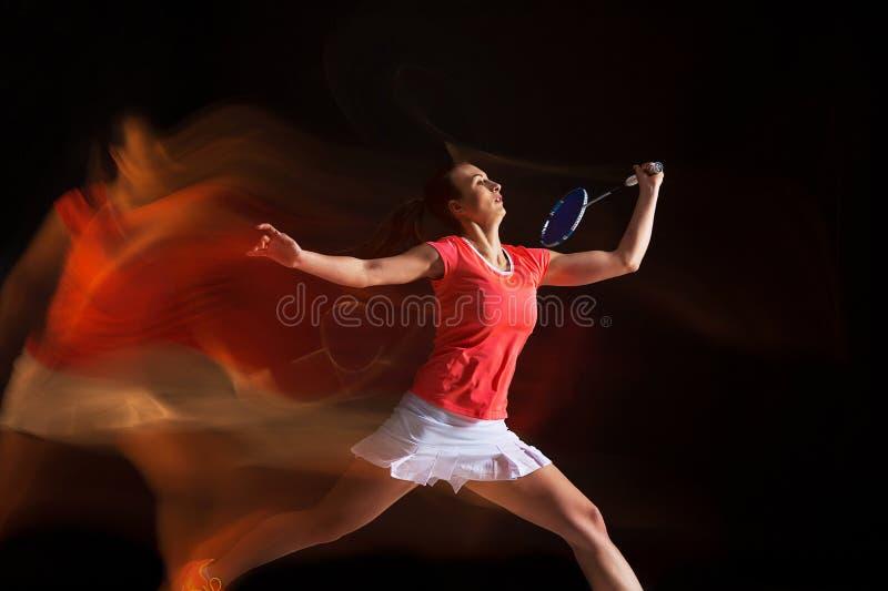 Młoda kobieta bawić się badminton nad czarnym tłem zdjęcia royalty free