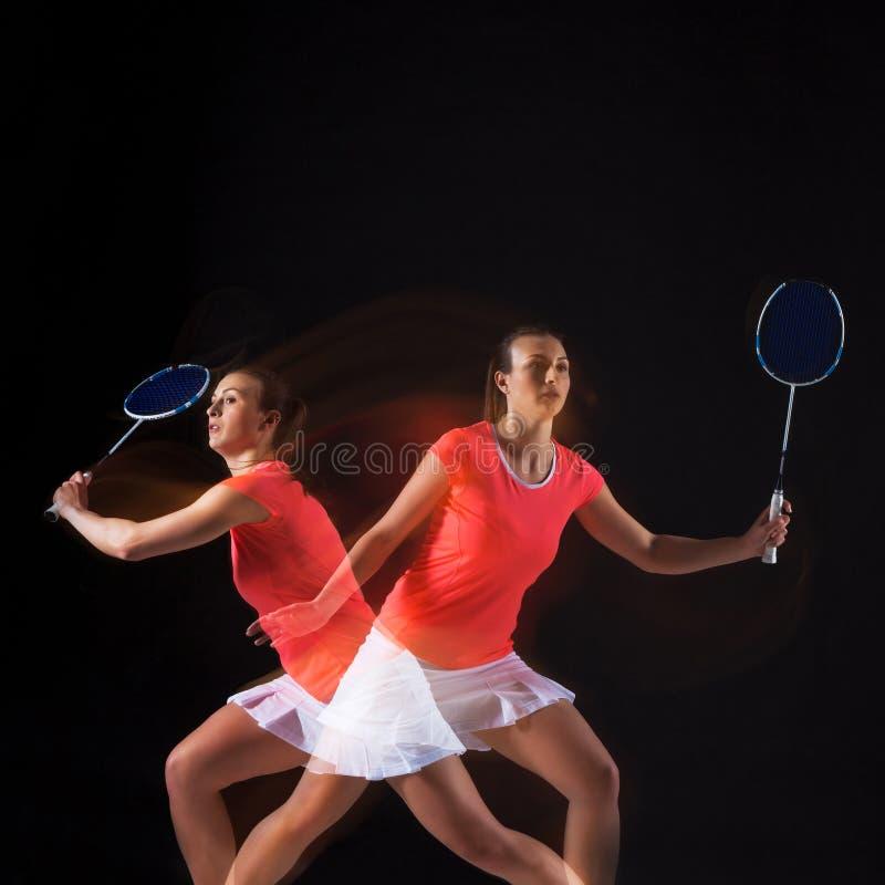 Młoda kobieta bawić się badminton nad czarnym tłem zdjęcia stock