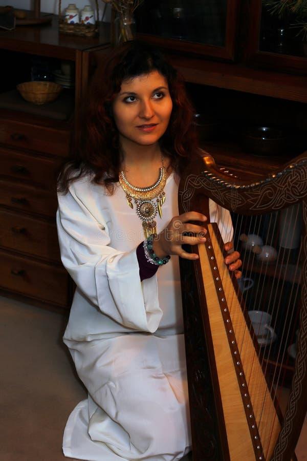 Młoda kobieta bawić się celt harfę w białym anielskim dziejowym kostiumu obraz royalty free