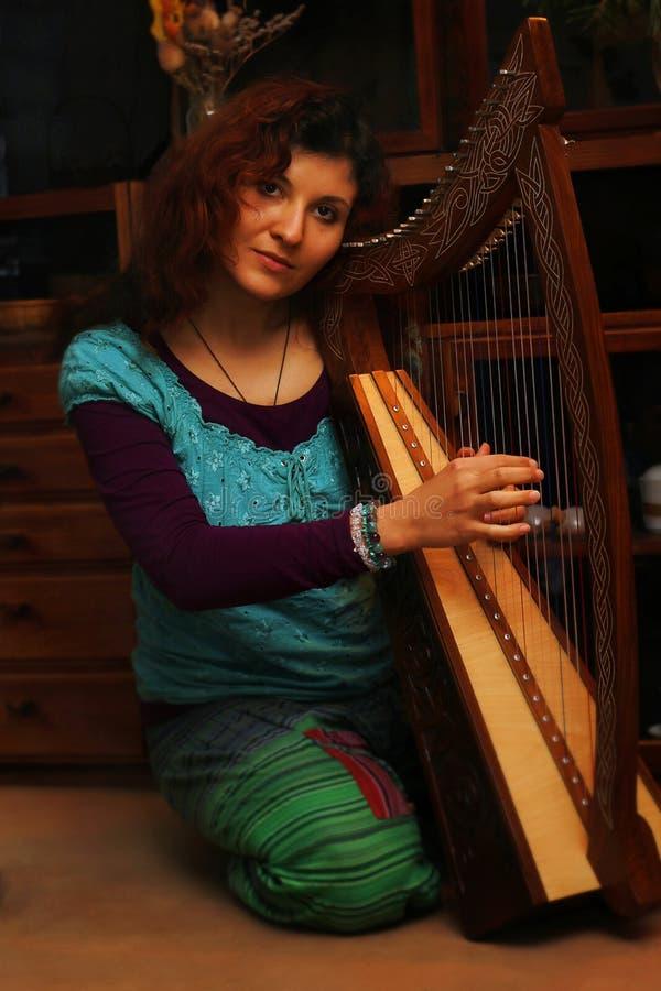 Młoda kobieta bawić się celt harfę w ethno kostiumu zdjęcia royalty free