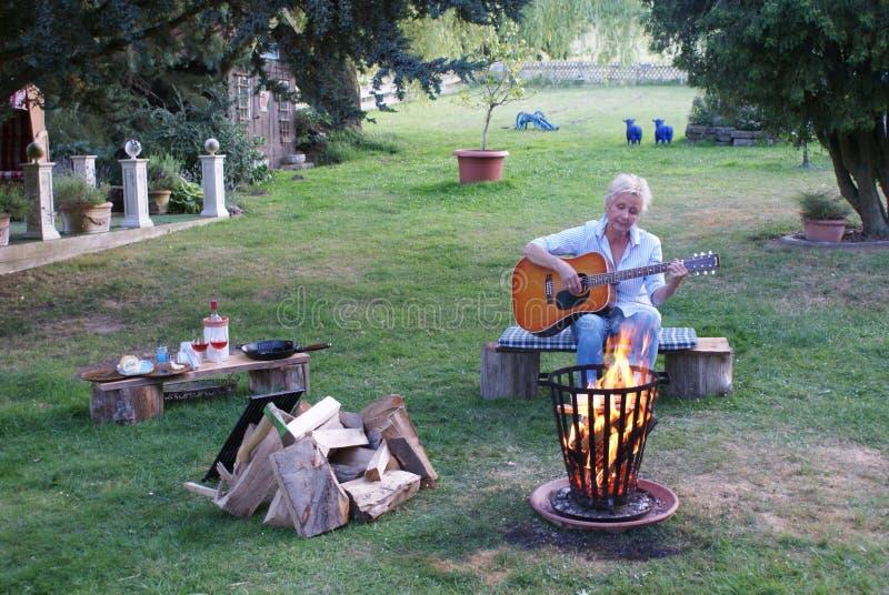 Młoda kobieta bawić się gitarę akustyczną podczas gdy siedzący blisko ogniska obrazy royalty free