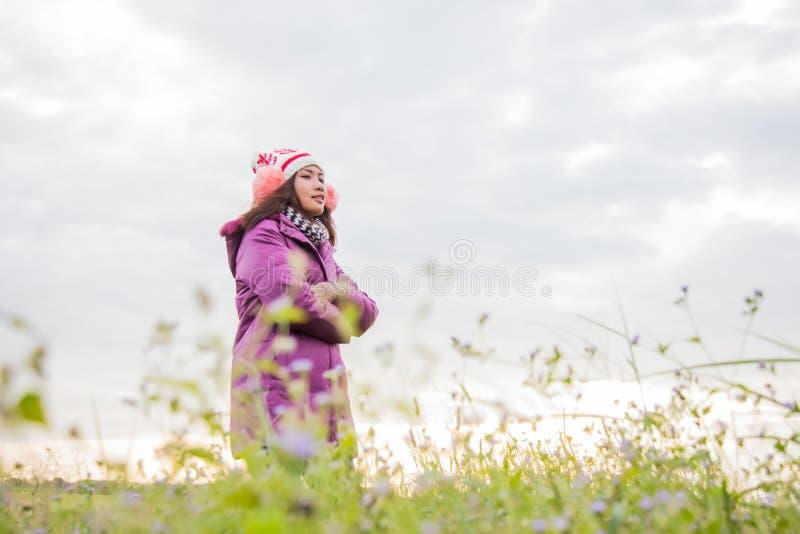 Młoda kobieta bawiła się na polu kwiatów w zimowym powietrzu fotografia stock