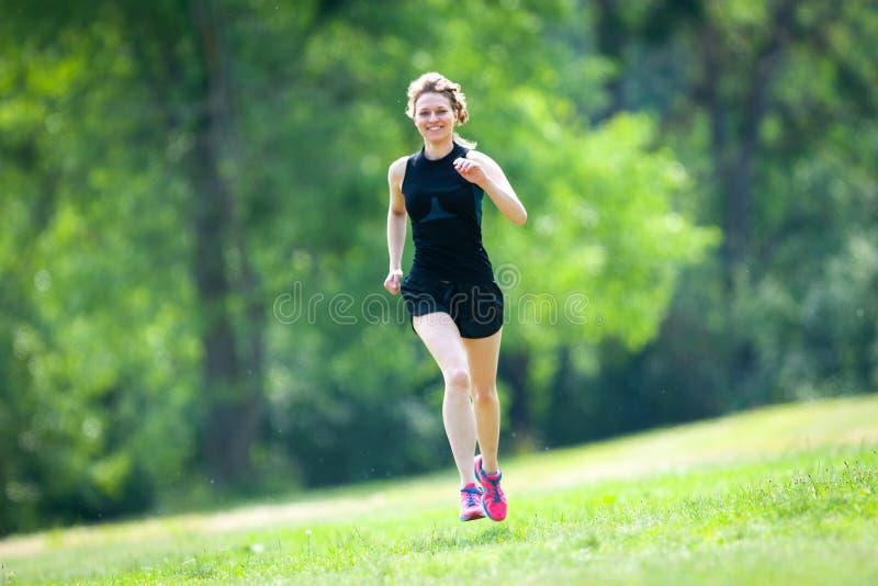Młoda kobieta biega przy parkiem obraz stock