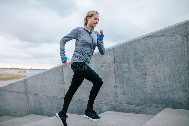 Młoda kobieta biega samotnie w górę schodków obraz stock