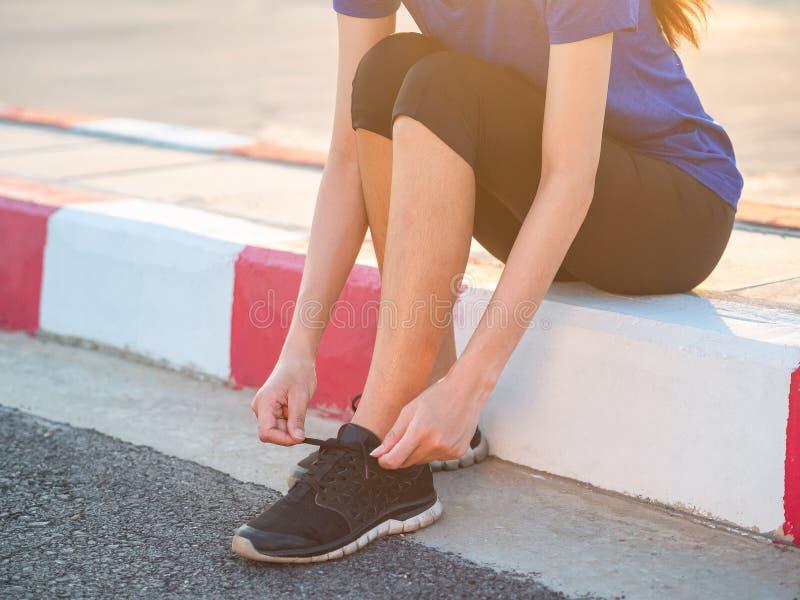 Młoda kobieta biegacz wiąże shoelace przed biegać obraz royalty free