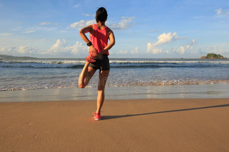 młoda kobieta biegacza rozciąganie iść na piechotę przed biegać na wschodu słońca nadmorski obraz royalty free