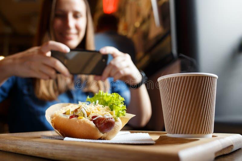 Młoda kobieta bierze fotografię jej lunch w kawiarni fotografia royalty free