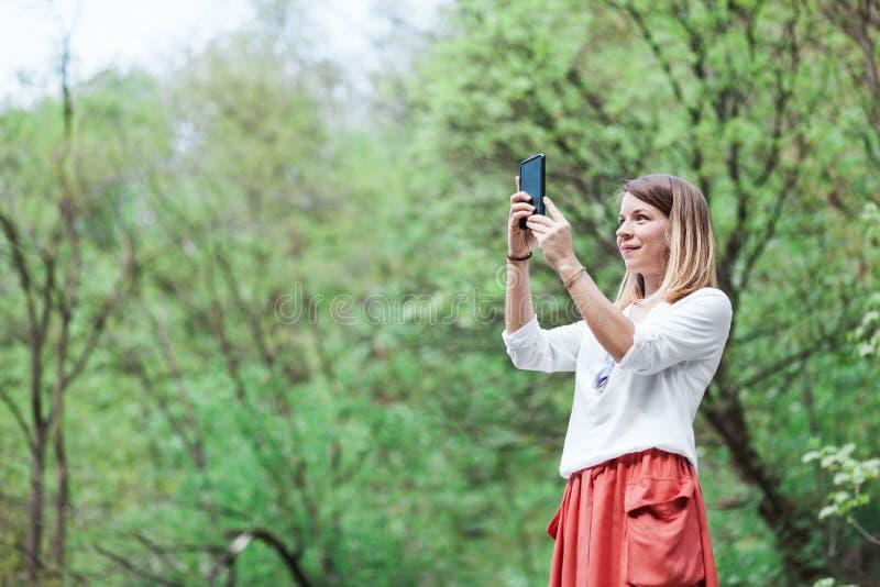 Młoda kobieta bierze fotografię na smartphone fotografia stock