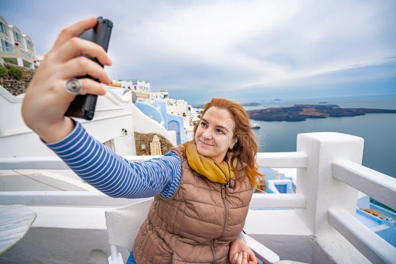 M?oda kobieta bierze fotografii selfie przy Grecja wyspami Santorini, jeden pi?kni podr??y miejsce przeznaczenia ?wiat zdjęcia royalty free