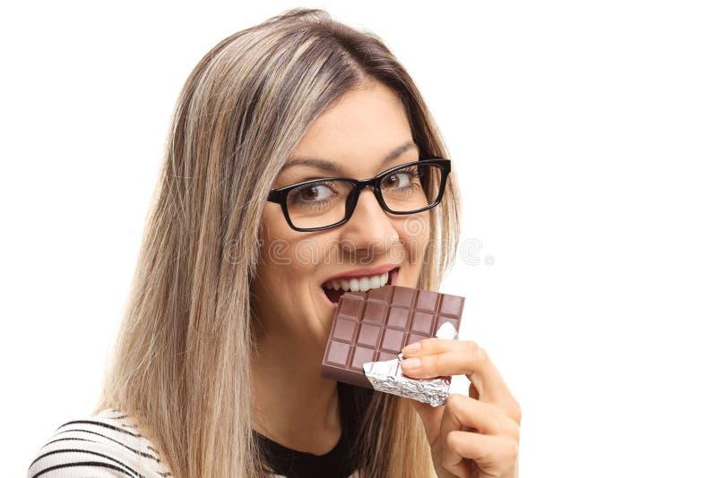Młoda kobieta bierze kąsek z czekoladowego baru zdjęcia stock