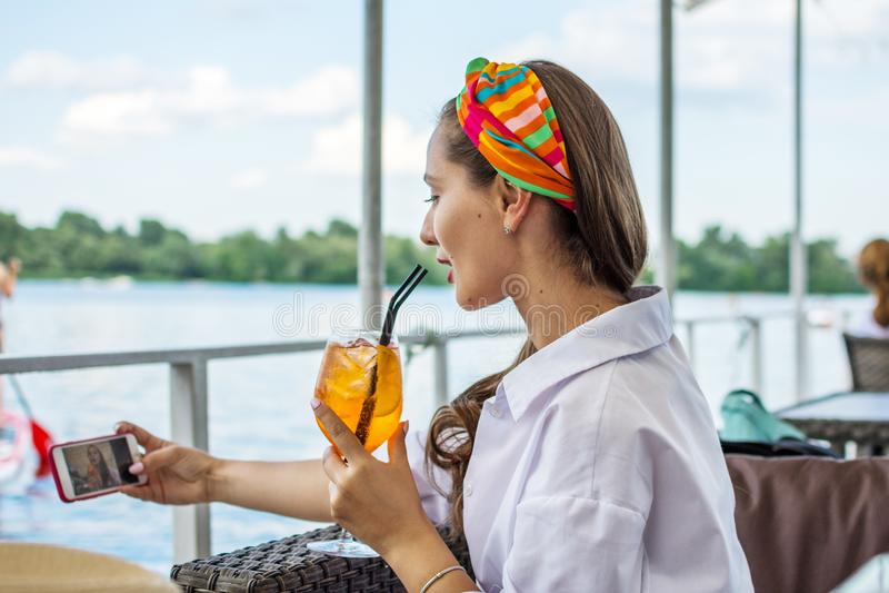 Młoda kobieta bierze selfie z telefonem komórkowym dla ogólnospołecznych sieci i napoju koktajlu fotografia royalty free