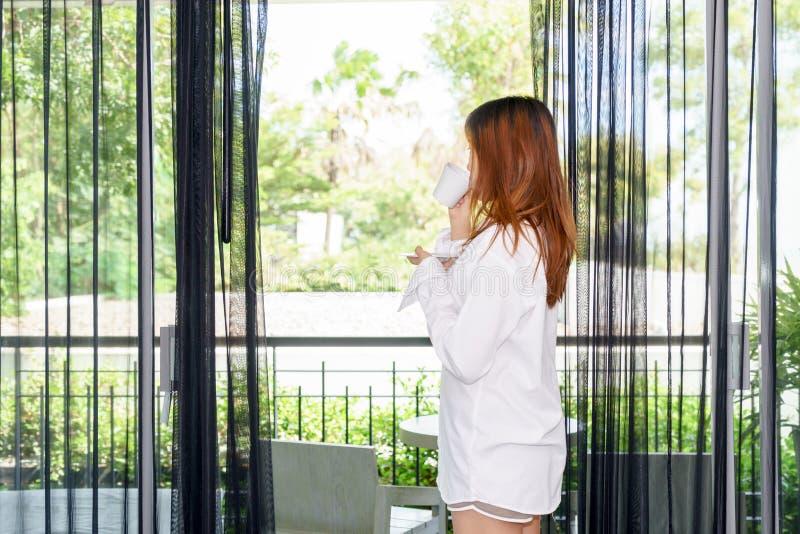 Młoda kobieta budził się up i pijący kawę lub herbaty pod światłem słonecznym g obraz royalty free