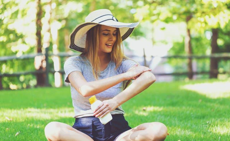 Młoda kobieta butelka sunblock outside fotografia stock