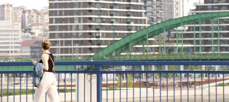 Młoda kobieta chodzi nad miasto mostem i patrzeje pejzaż miejski panoramę obraz stock