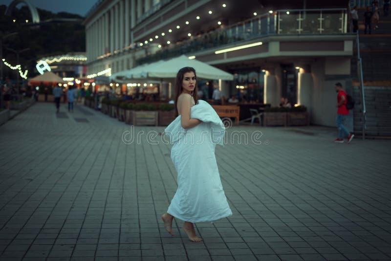 Młoda kobieta chodzi wokoło miasta w białej koc zdjęcia stock