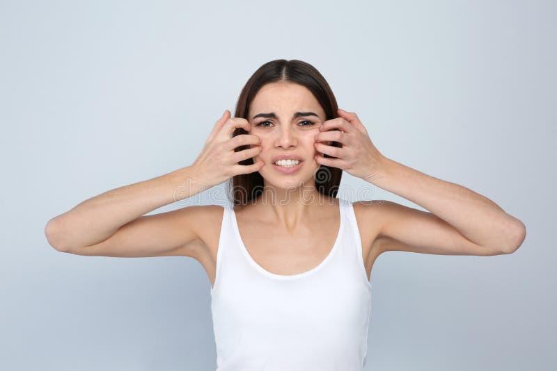 Młoda kobieta chrobota twarz na lekkim tle zdjęcie royalty free