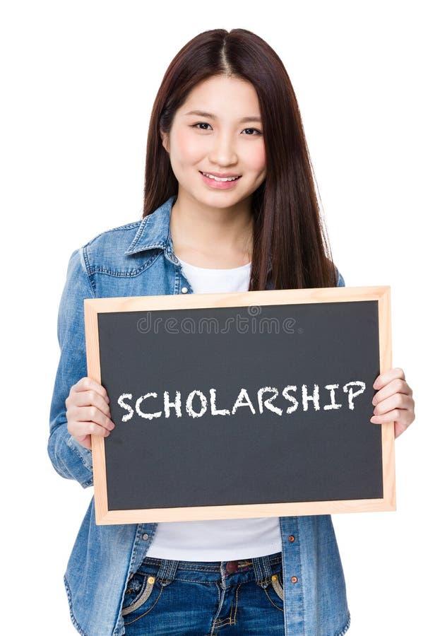Młoda kobieta chwyt z chalkboard pokazuje słowo stypendium zdjęcie stock