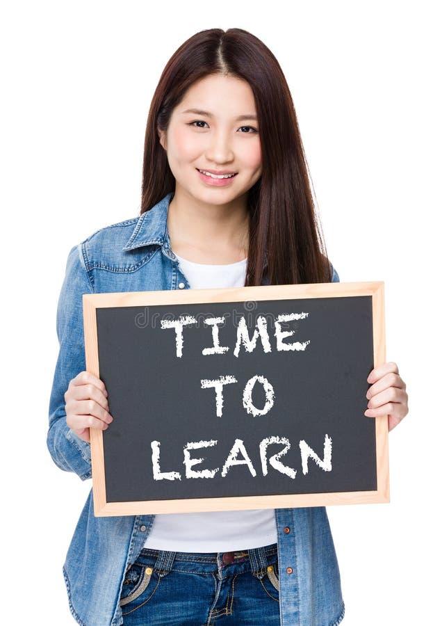Młoda kobieta chwyt z chalkboard seansu zwrotem czas uczyć się obraz royalty free