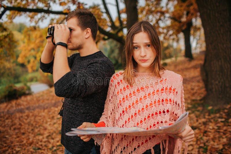 Młoda kobieta chwyta spojrzenie przy camer i mapa udaremnia Faceta spojrzenie w lornetkach One bada obrazy stock
