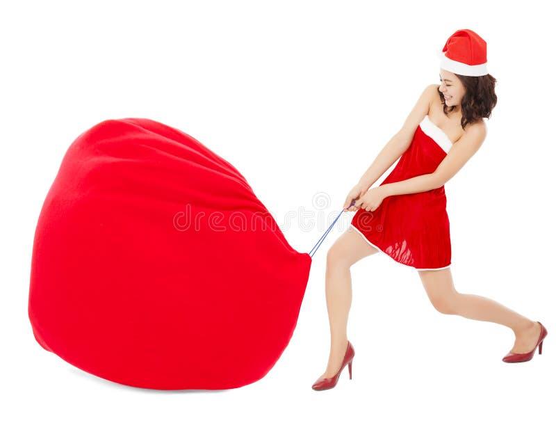 Młoda kobieta ciągnie ciężką i dużą prezent torbę zdjęcia stock