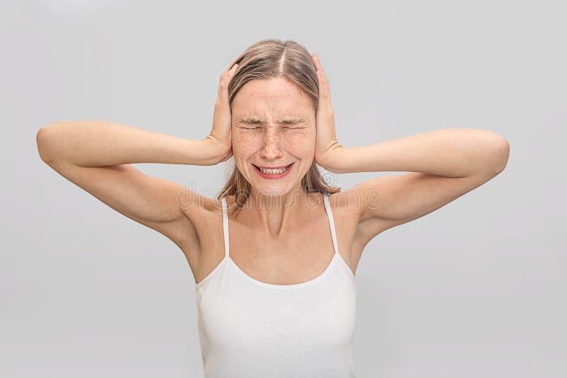 Młoda kobieta cierpi od migreny Coveres ucho z rękami i utrzymaniami przygląda się zamkniętego Młoda kobieta jest ubranym białą k zdjęcia royalty free
