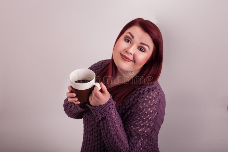 Młoda kobieta cieszy się kubek gorąca kawa obrazy stock