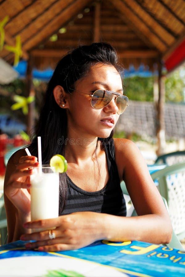 Młoda kobieta cieszy się napój w plażowej restauraci w Tajlandia zdjęcie stock